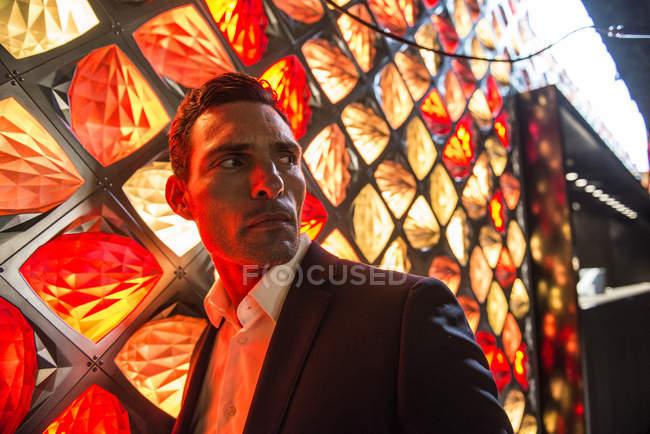 Homme baigné dans la lumière rouge devant le luminaire — Photo de stock