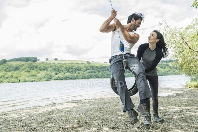 Мужчина и женщина на шинах, свисающие с деревьев — стоковое фото