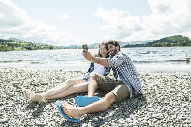 Мужчина и женщина берет selfie на берегу — стоковое фото