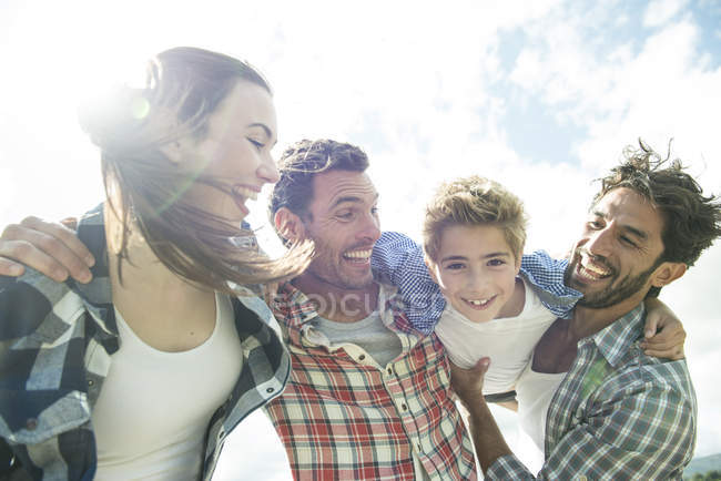 Four people smiling on shore — Stock Photo