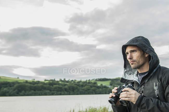 Man using binoculars on shore — Stock Photo