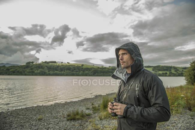Man standing with binoculars on shore — Stock Photo