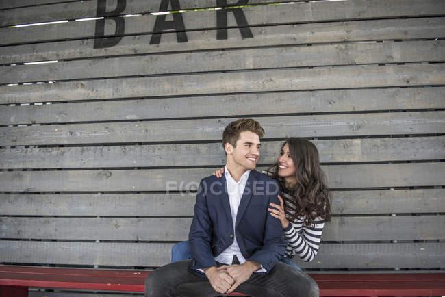 Paar sitzt auf Bank hinter Bar — Stockfoto