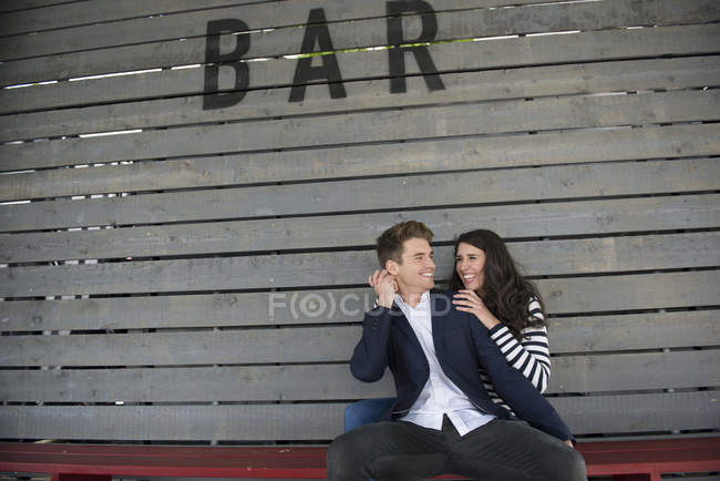 Couple sitting on bench behind bar — Stock Photo