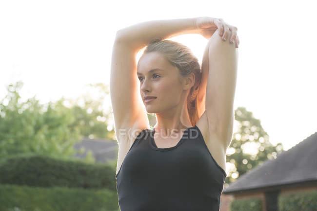 Mujer haciendo ejercicios de estiramiento en la cancha de tenis - foto de stock