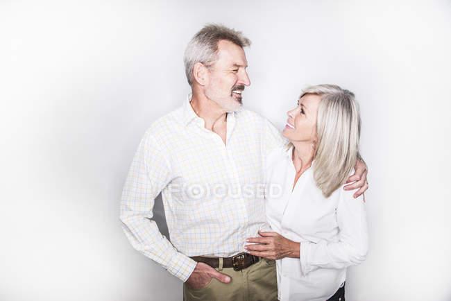 Paar umarmt und lächelnd in die Kamera — Stockfoto
