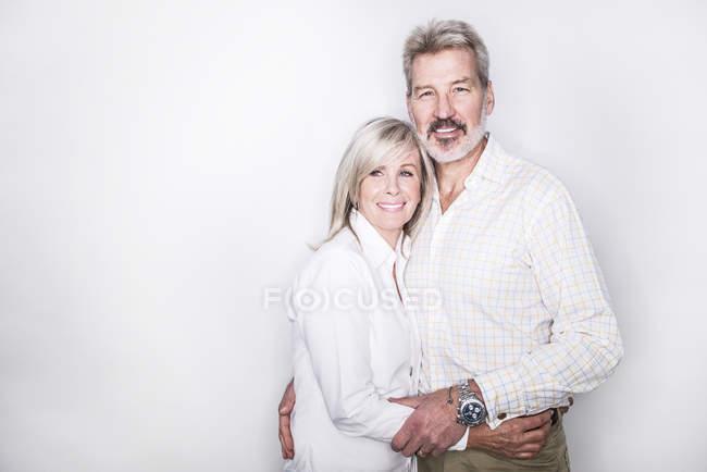 Пара обіймати і посміхається на камеру — стокове фото