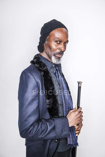 Uomo africano in piedi con la canna — Foto stock