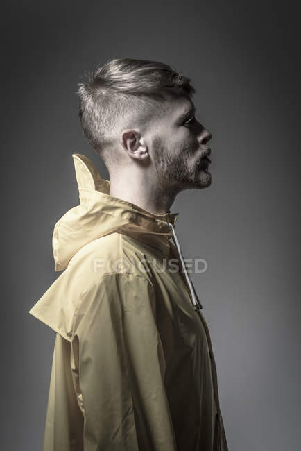 Barbu homme dans jaune vent tricheur — Photo de stock