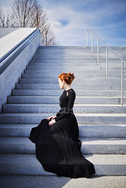 Woman sitting on steps in black gown — Stock Photo