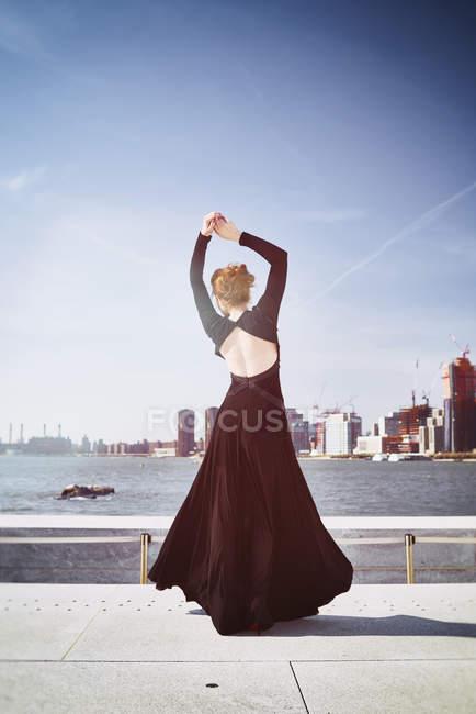 Mulher em pé de vestido preto na parede de mármore — Fotografia de Stock
