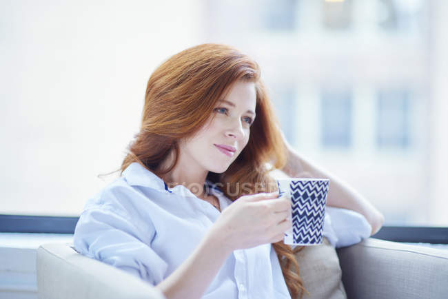 Mujer en camisa blanca bebe café de la mañana - foto de stock
