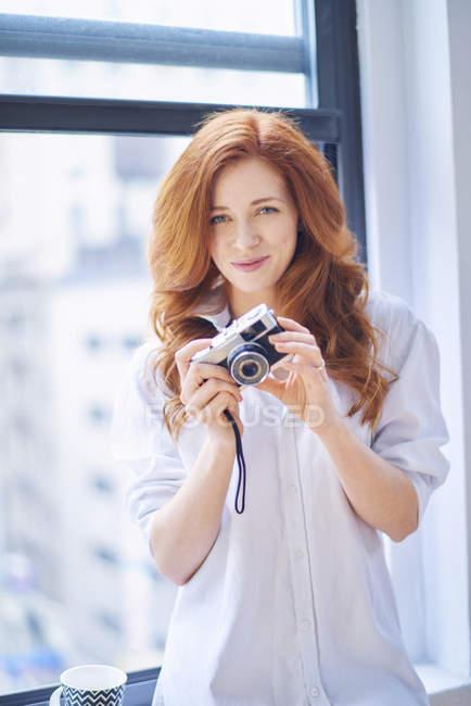 Mujer en camisa blanca sostiene la cámara vintage - foto de stock