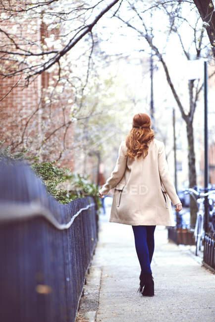Frau im Kamelmantel geht an Geländer vorbei — Stockfoto