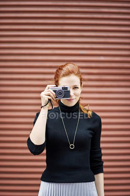 Женщина с классические камеры напротив двери гаража — стоковое фото