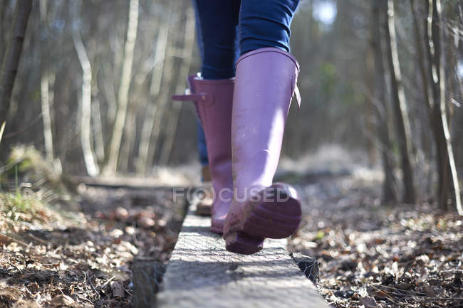 Female legs in gumboots in forest — Stock Photo