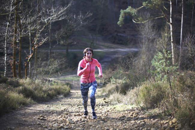 Woman jogging uphill — Stock Photo