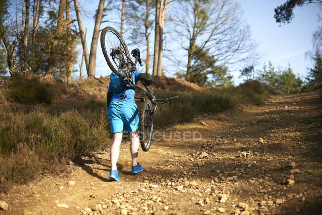 Человек перевозящих горный велосипед — стоковое фото