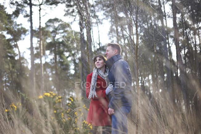 Pareja abrazándose en el bosque - foto de stock