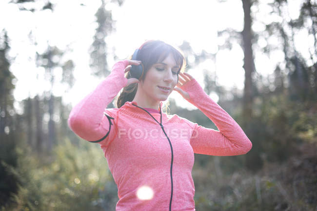 Woman prepares to go for run in woods — Stock Photo