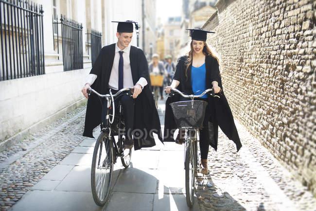 Giovani studenti in abiti di laurea ciclismo — Foto stock