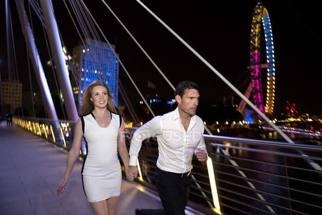 Couple courir à travers Millennium Bridge — Photo de stock