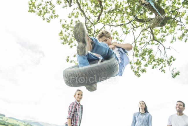 Семья, играя на шинах, свисающие с деревьев — стоковое фото