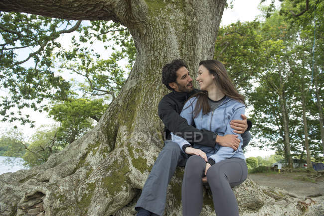 Two lovers cuddling in tree — Stock Photo