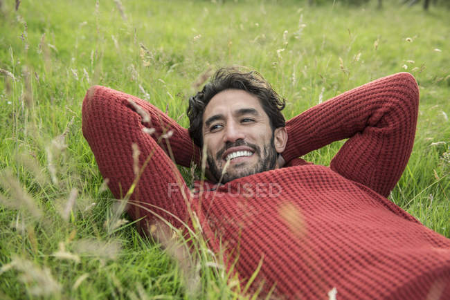 Uomo in maglione rosso rilassante in erba — Foto stock