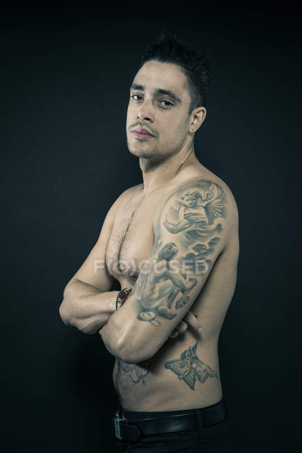 Tattooed man posing with arms crossed — Stock Photo