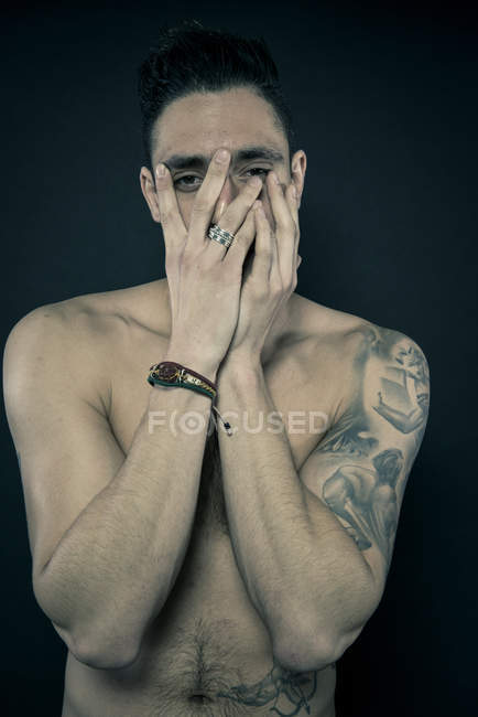 Tattooed man covering face with hands — Stock Photo