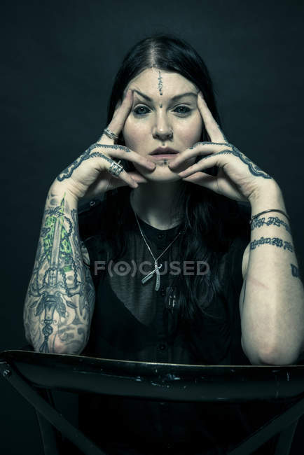 Portrait of woman with tattooed arms and face — Stock Photo