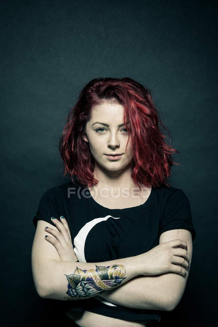 Woman standing with tattooed crossed arms — Stock Photo