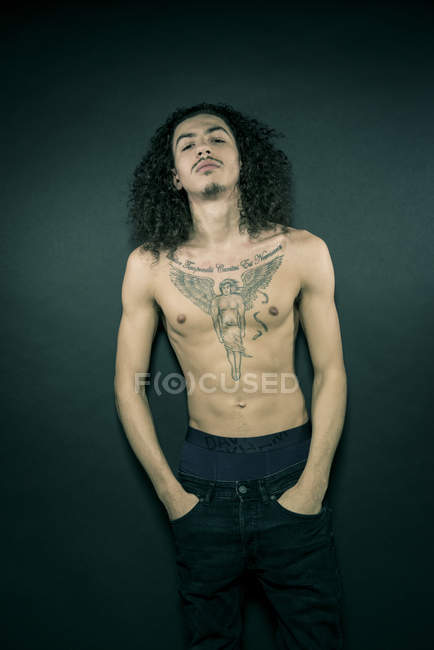 Portrait of man with tattooed chest and long hair — Stock Photo