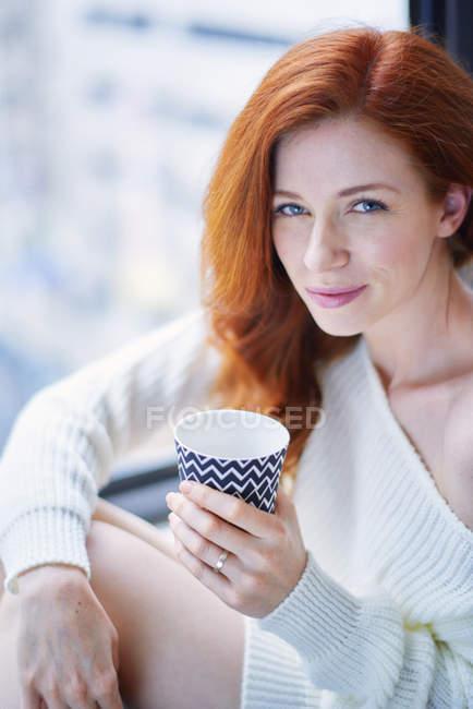 Женщина с горячим напитком, сидя у окна — стоковое фото
