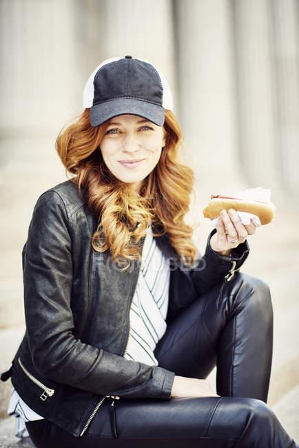 Mujer en gorra de béisbol comiendo hot dog - foto de stock