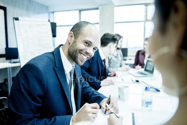 Profissionais sentados em ambiente de escritório — Fotografia de Stock