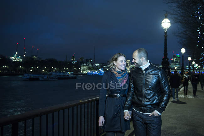 Couple hold hands walking along South Bank — Stock Photo