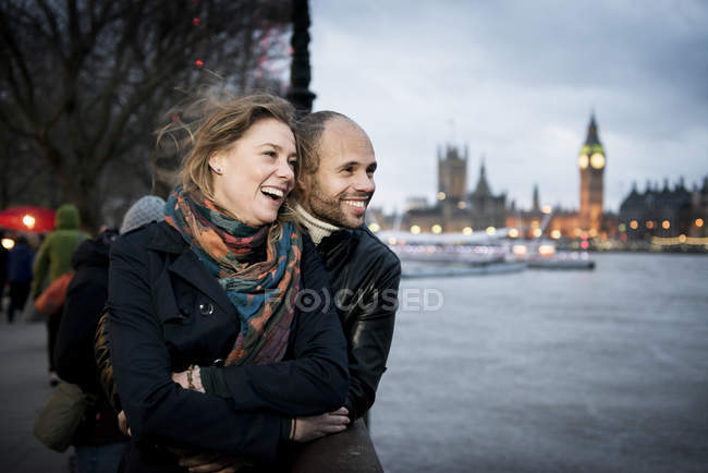 Couple standing looking across River Thames — Stock Photo