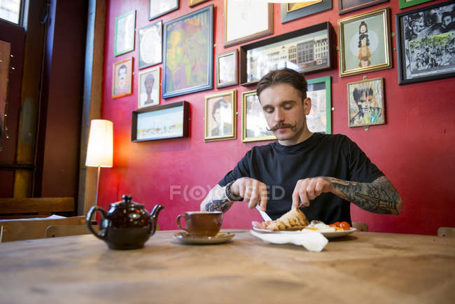 Man eating at in coffee shop — Stock Photo