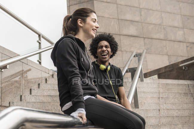 Couple laughing while sitting on handrail — Stock Photo