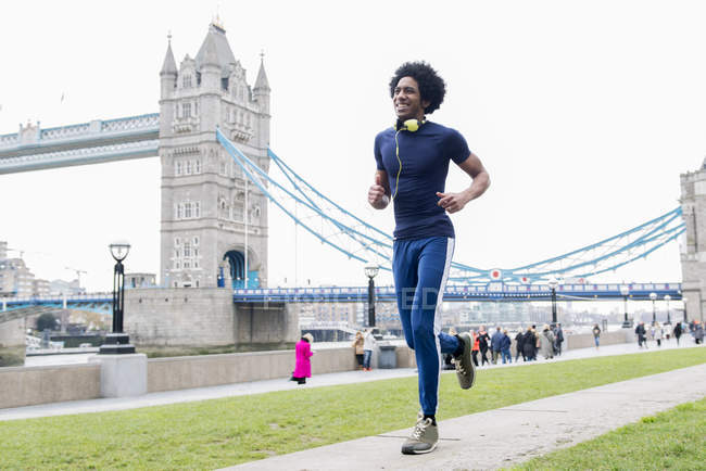 Man jogging past Tower Bridge — Stock Photo