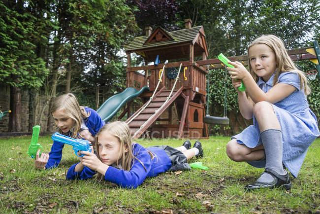 Дівчаток, грати з води пістолетів — стокове фото
