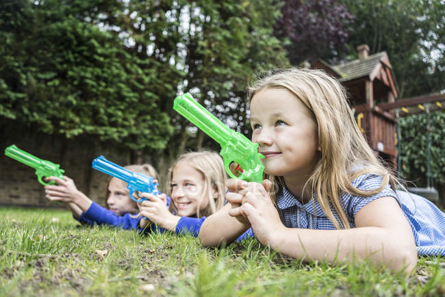 Girls playing with water pistols — Stock Photo