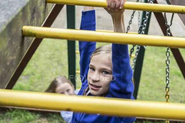Girl climbing on playground apparatus — Stock Photo