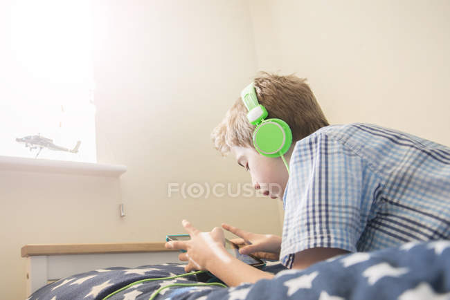 Boy listening music in headphones — Stock Photo