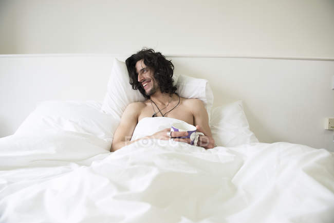 Man with long hair lying in bed with cup of tea — Stock Photo