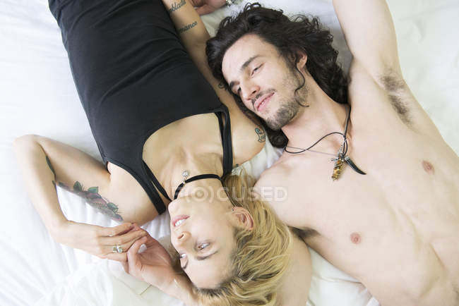 Tattooed couple lying together on bed — Stock Photo