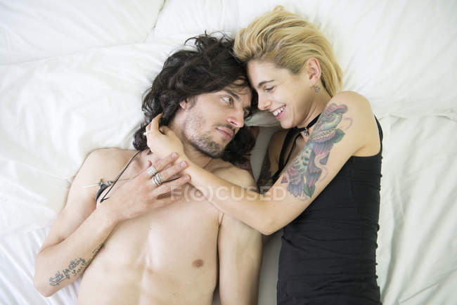 Tattooed couple cuddling on bed — Stock Photo