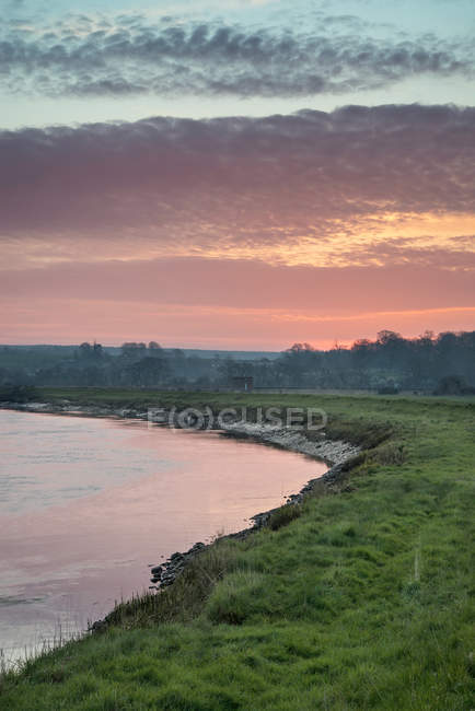 Sunrise reflected in calm river — Stock Photo